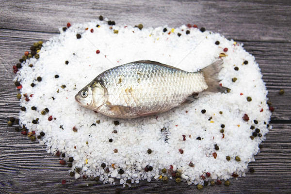 A  fresh carp live fish lying on a on salt and pepper background with slices of lemon and with salt  Stock photo © mcherevan