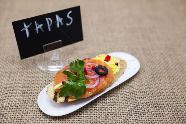 TAPAS poster . Fresh Spanish tapas on bread baguette smoked Norwegian salmon with black olive butter Stock photo © mcherevan