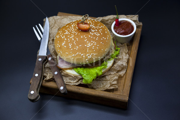 Classical American fresh juicy burger with chicken and ham on a wooden tray with a spicy chili sauce Stock photo © mcherevan