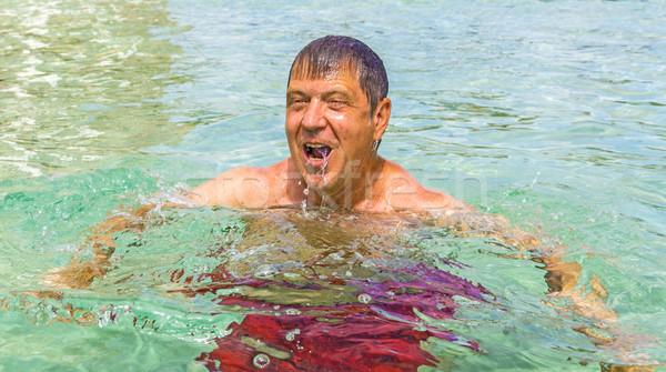 Férfi jókedv úszik óceán jóképű férfi tengerpart Stock fotó © meinzahn