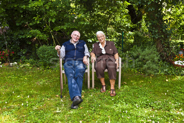 elderly couple sitting hand in hand in their garden Stock photo © meinzahn