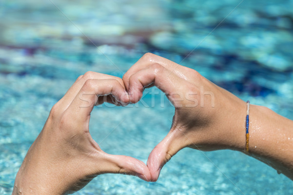 young man shows love sign with heart shape formed by hands Stock photo © meinzahn
