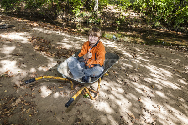 child sits in the wheel barrow and relaxes Stock photo © meinzahn
