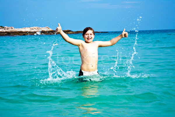 boy is enjoying the clear warm water at the beautiful beach but  Stock photo © meinzahn