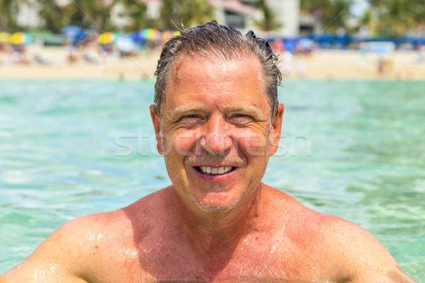 Jóképű férfi jókedv úszik óceán tengerpart család Stock fotó © meinzahn