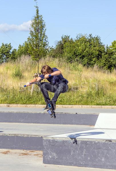 boy has fun riding his push scooter Stock photo © meinzahn