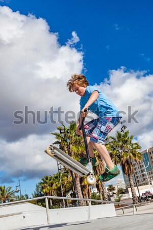 boy enjoys jumping with his push scooter over a barriere Stock photo © meinzahn