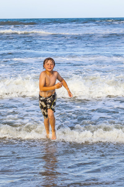 young boy running through the water at the beach Stock photo © meinzahn