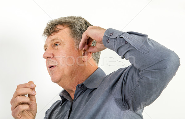 serious man in shirt handling his  hearing aid  Stock photo © meinzahn