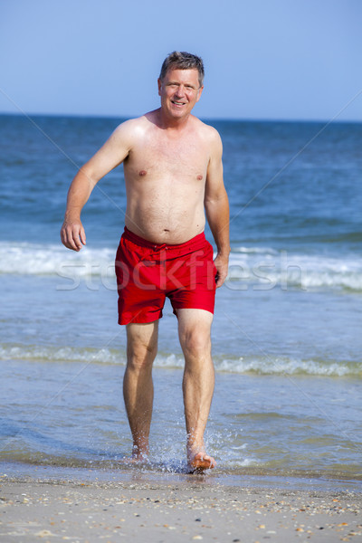 handsome man walking at the  beach Stock photo © meinzahn