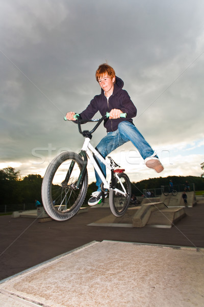 young red haired boy is jumping with his BMX Bike at the skate p Stock photo © meinzahn