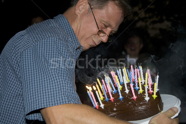 man blows out his birthday candles at the birthday Stock photo © meinzahn