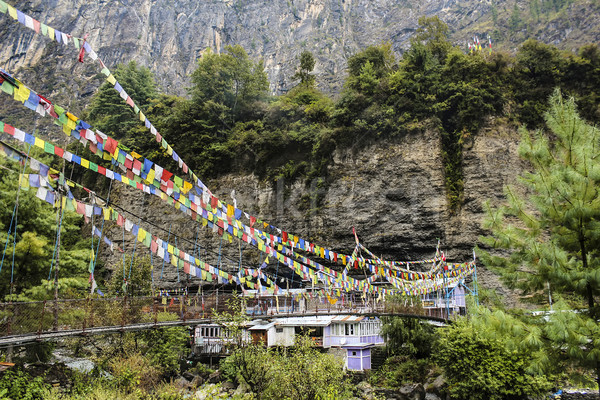 Suspension bridge with prayer flags in the village Stock photo © meinzahn