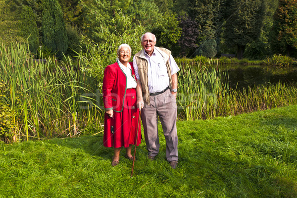 elderly couple standing hand in hand in their garden Stock photo © meinzahn