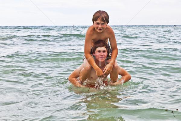 boys having fun in the beautiful clear sea Stock photo © meinzahn