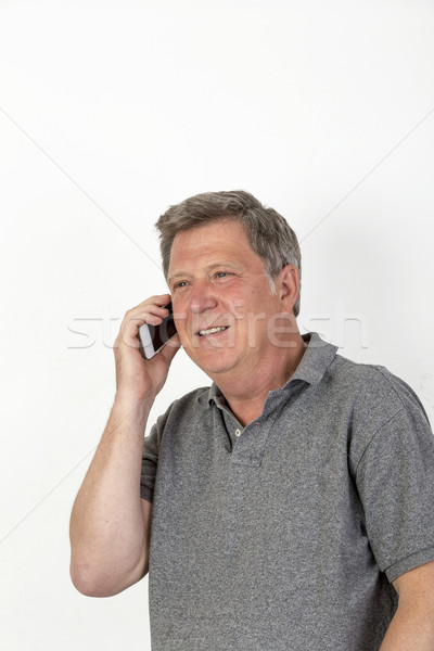 smiling mature man with grey polo shirt at the mobile Stock photo © meinzahn