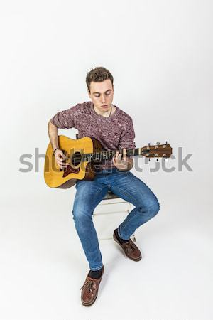 teenage guitar player sits on a chair and plays western guitar Stock photo © meinzahn