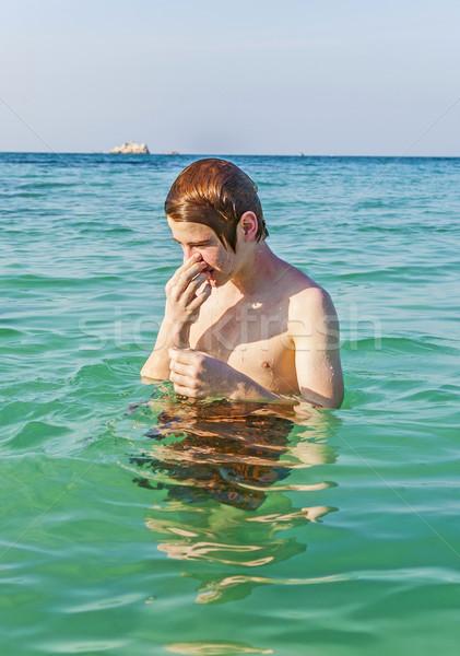 sneezing boy swimming in the  ocean Stock photo © meinzahn