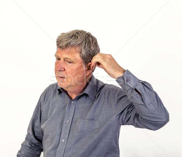 man  puts hearing aid in the ear Stock photo © meinzahn