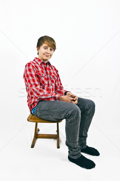 friendly looking young boy with red shirt sitting on a wooden sc Stock photo © meinzahn