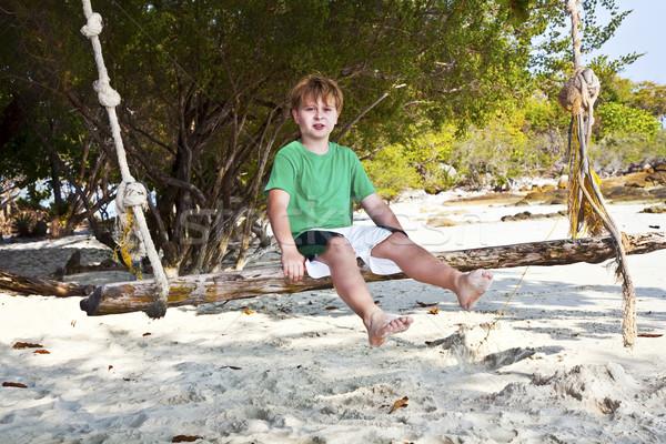 Erkek oturma salıncak plaj ağaçlar gülümseme Stok fotoğraf © meinzahn