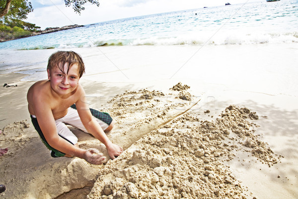 happy boy is building a canal out of sand at the bea Stock photo © meinzahn