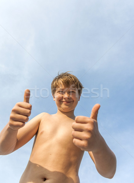 happy smiling young boy  gives fingersign thumbs-up Stock photo © meinzahn