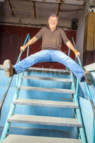 man jumping down the stairs of an old waterless pool Stock photo © meinzahn