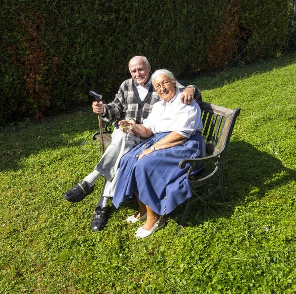 elderly couple sitting in their garden and enjoy life Stock photo © meinzahn