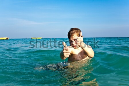 boy is swimming on his surfboard and happily smiling in  a beaut Stock photo © meinzahn