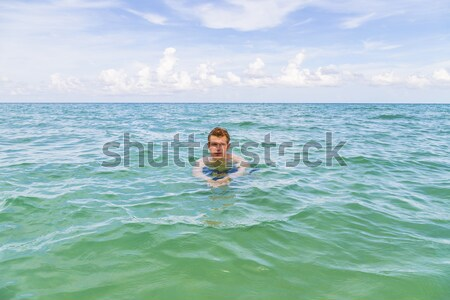boy with red hair is enjoying the clear warm water at the beauti Stock photo © meinzahn