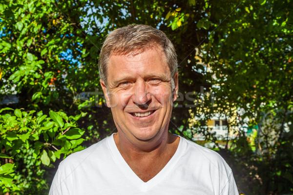 Szczęśliwy atrakcyjny człowiek ogród portret drzewo Zdjęcia stock © meinzahn