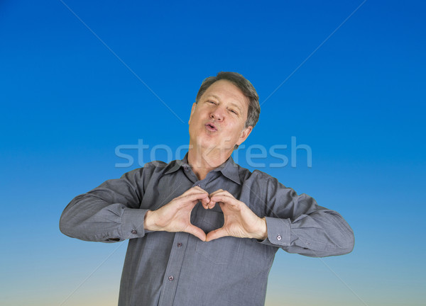 man gives a kiss in the air and shows heart sign with hands Stock photo © meinzahn