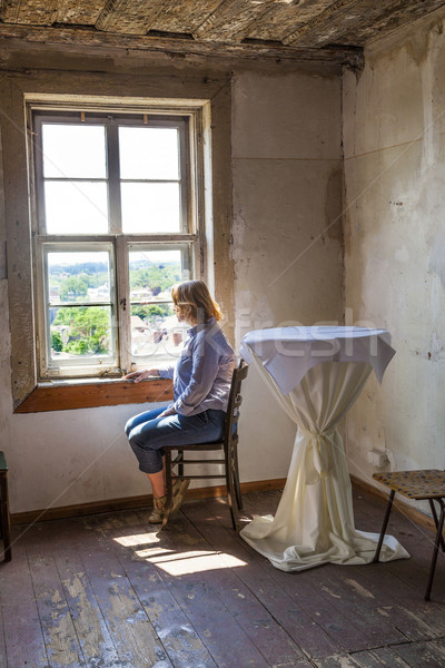 woman sitting at the window of an old house Stock photo © meinzahn