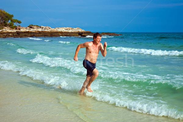 man is running along the beautiful beach, enjoying the water Stock photo © meinzahn