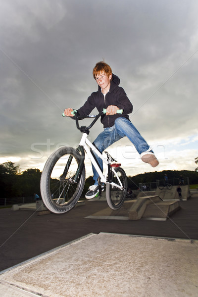 joung red haired boy is jumping with his BMX Bike Stock photo © meinzahn