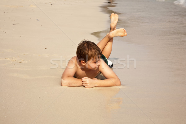 boy iy lying at the beach and enjoying the warmness of the water Stock photo © meinzahn