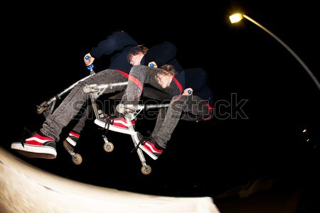 Stock photo: young boy jumpy with his scooter by night with stroboscope