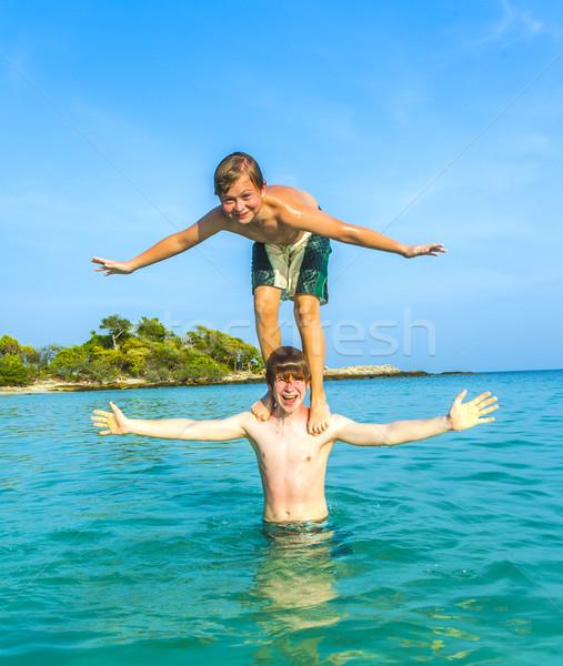 Erkek eğlence oynama omzunda okyanus gökyüzü Stok fotoğraf © meinzahn