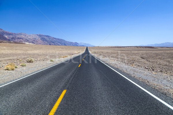 Death Valley road straight across the desert to the mountains in Stock photo © meinzahn