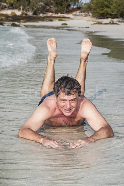 Férfi tengerpart élvezi sósvízi pici hullámok Stock fotó © meinzahn