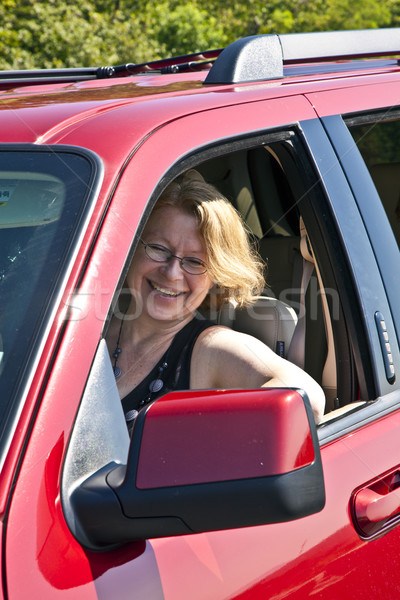 Stock photo: smiling woman drives a red car