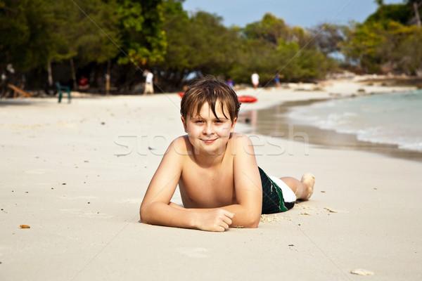 happy boy lying at the beach Stock photo © meinzahn