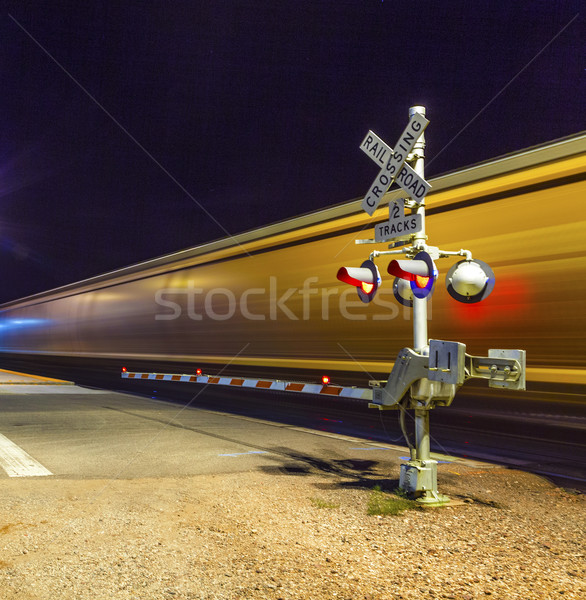 Railroad crossing with passing train by night  Stock photo © meinzahn