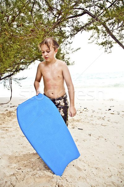 young boy at the beach with surf board is smiling and looking se Stock photo © meinzahn