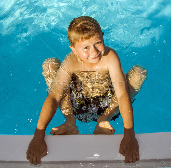 cute boy in swimming pool laughes and poses  Stock photo © meinzahn