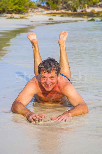 Man in bathingsuit is lying at the beach and enjoying the saltwater with tiny waves and smiles Stock photo © meinzahn