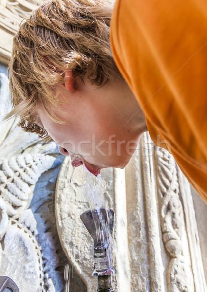 Boy is drinking water on a public fountain  Stock photo © meinzahn