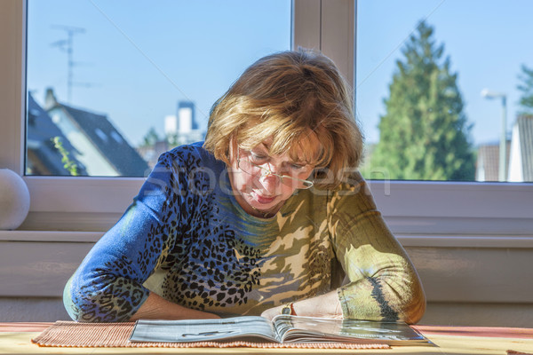 elderly attractive woman reading in a magazine Stock photo © meinzahn