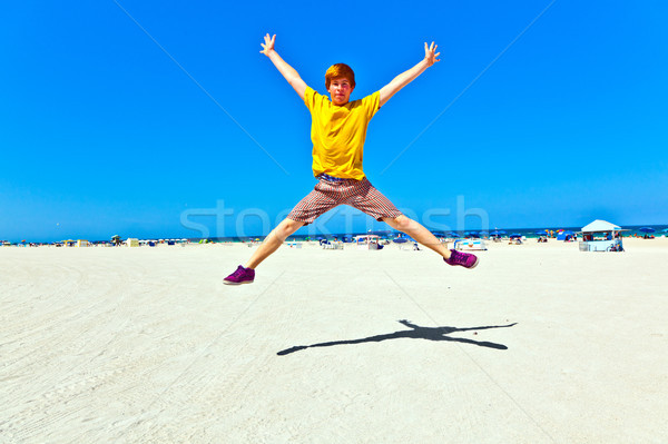 Stock photo: cute boy jumping in the air at the beach in south Miami
